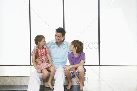 Sitting on lap : Father with son  7-9  and daughter  5-6  sitting indoors