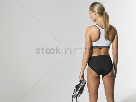 Young woman : Female athlete standing holding shoes back view