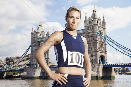 Proud : Female athlete standing in front of tower bridge