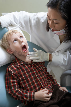 Young boy : Female dentist examining boy  6-9  in surgery