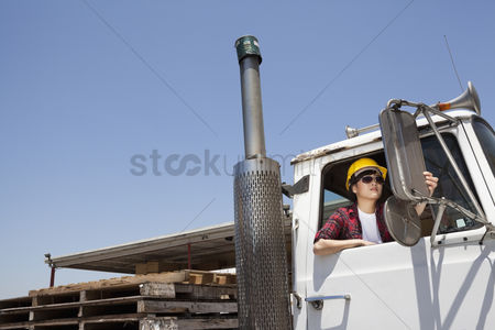 Land : Female industrial worker adjusting mirror while sitting in logging truck