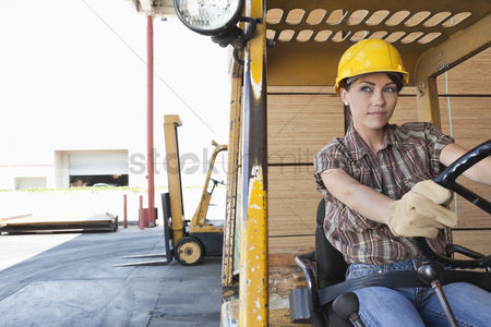 Forklift : Female industrial worker driving forklift truck