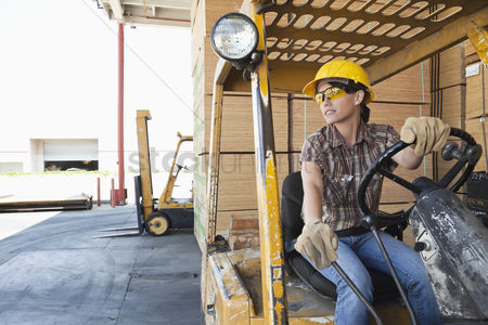 Forklift : Female industrial worker looking away while driving forklift truck
