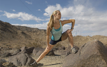 Sports : Female jogger stretching in mountains