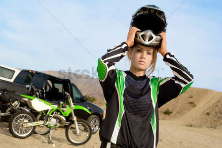Sports : Female motocross racer in desert  portrait