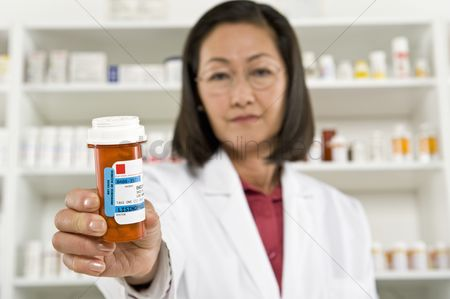 Medication : Female pharmactist holding prescription drugs