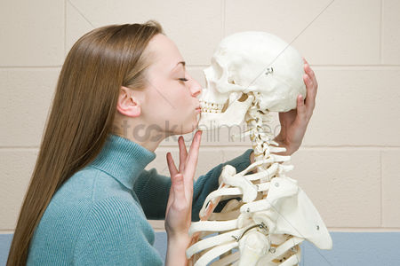 Kissing : Female student kissing a human skeleton
