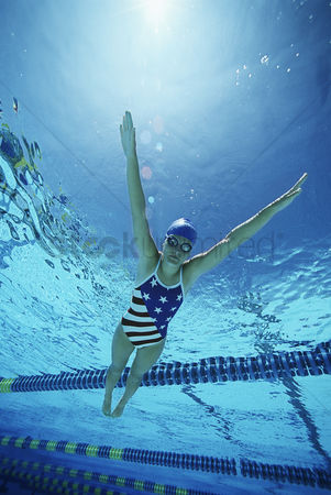 Swimmer : Female swimmer wearing united states swimsuit swimming in pool