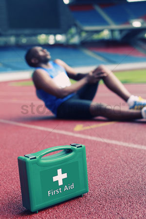Pain : First aid kid  male athlete clasping leg in pain in the background