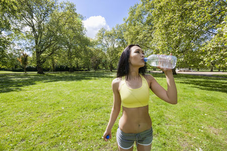 Summer : Fit young woman drinking water after jogging in park