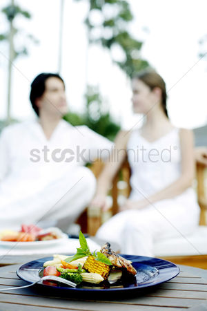 Girlfriend : Focus on a mouth-watering meal with a couple sitting in the background