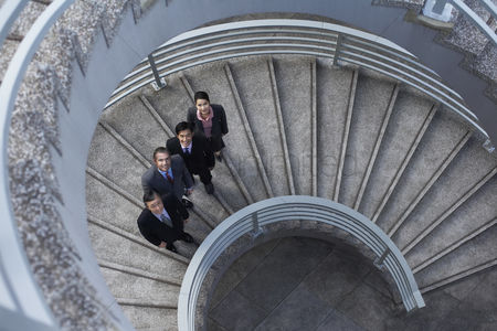 Steps : Four business associates standing on spiral staircase portrait