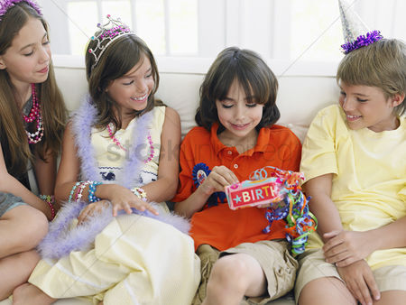 Birthday present : Four children  7-12  sitting on sofa at birthday party one opening present