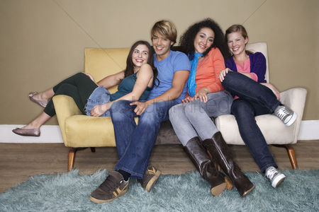Denim : Friends sitting arms around one another on sofa