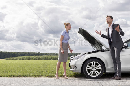 Land : Full length of business couple having argument by broken car at countryside