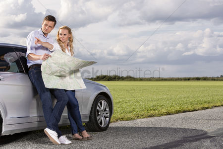 Land : Full length of couple with map discussing direction while leaning on car at countryside