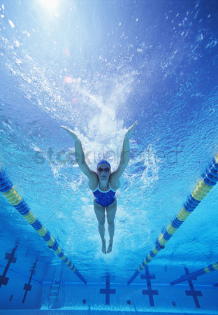 Swimmer : Full length of female swimmer in united states swimsuit swimming in pool