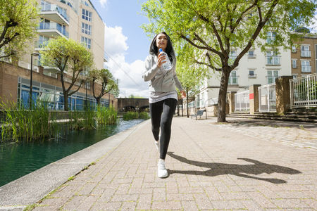 Asian : Full length of fit young woman jogging by canal against buildings