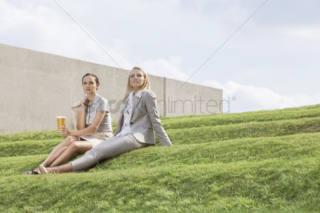 Steps : Full length of relaxed businesswomen in formals sitting on grass steps against sky