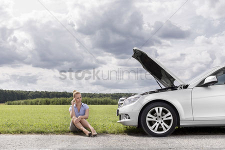 On the road : Full length of worried businesswoman sitting by broken down car at countryside