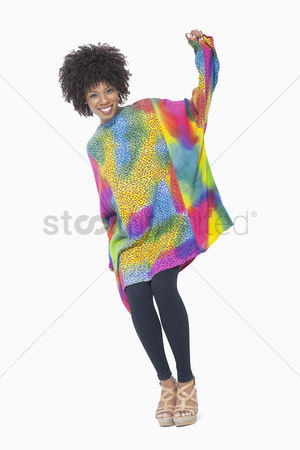 Traditional clothing : Full length portrait of an african american woman in dashiki standing over gray background