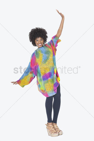 Dancing : Full length portrait of happy african american woman in dashiki dancing over gray background