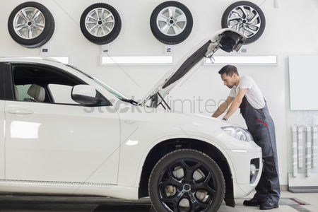 Transportation : Full length side view of male mechanic examining car engine in repair shop