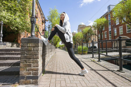 Jacket : Full length side view of young fit woman stretching on sidewalk