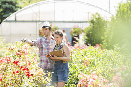 Examination : Gardener discussing with supervisor outside greenhouse