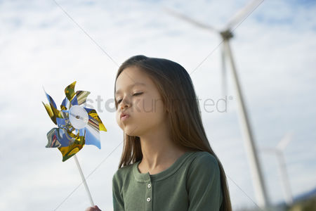 Blowing : Girl  5-6  blowing toy windmill at wind farm