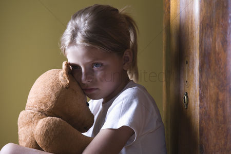 Ponytail : Girl embracing teddy bear in home