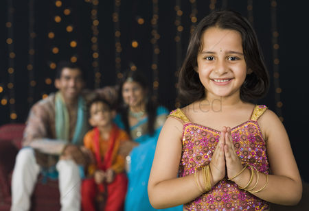 Diwali : Girl greeting on diwali festival with her family in the background