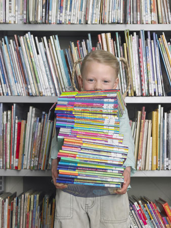 Learning : Girl holding stack of books in library portrait