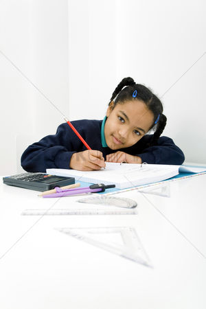 School children : Girl looking at camera while writing