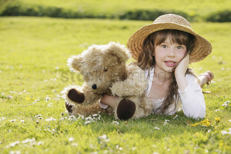 Grass : Girl lying on the grass with her teddy bear