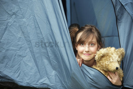 Lying forward : Girl relaxing in the tent with her teddy bear