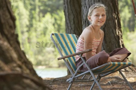 Posed : Girl sitting on deckchair in forest