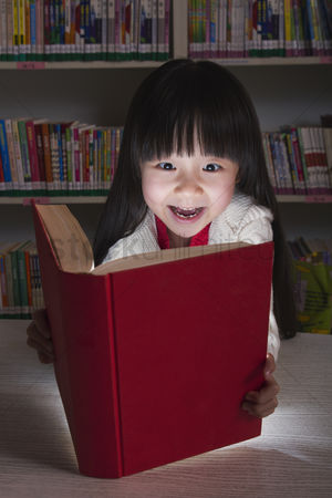 Amazed : Girl surprised by glowing book