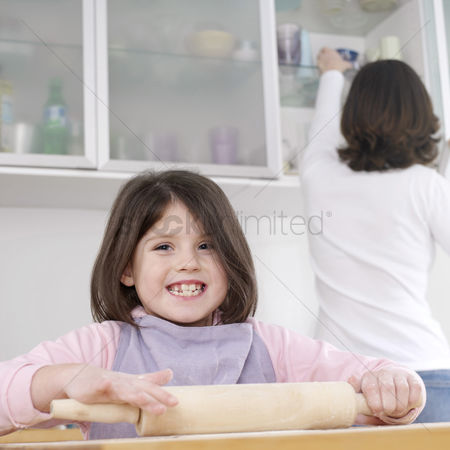 Learning : Girl using rolling pin with her mother in the background