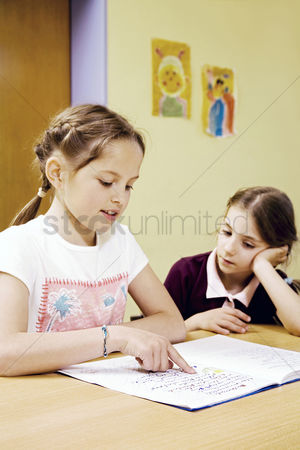 School children : Girl watching her friend reading book