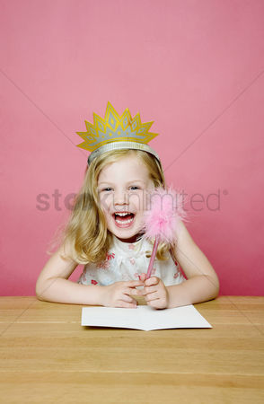 Satisfaction : Girl with crown smiling while holding a pencil