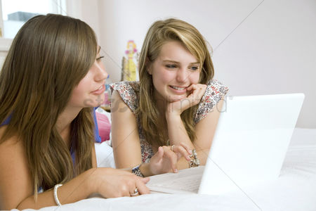 Lying forward : Girls lying forward on the bed using laptop