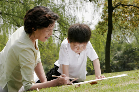 Two people : Grandmother and grandson painting picture in the park