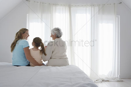 White hair : Grandmother mother and daughter sitting on bed in bedroom