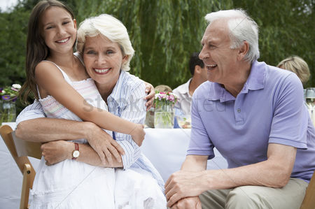 Relationships : Grandparents with granddaughter  10-12  sitting at table in garden