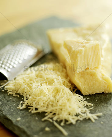 Flavour : Grated parmesan cheese on a wooden board with grater