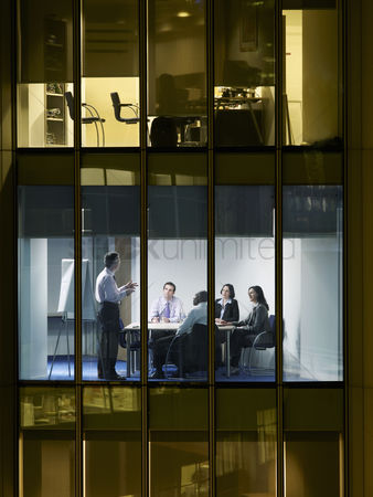 Leadership : Group of business people at meeting in office view from building exterior