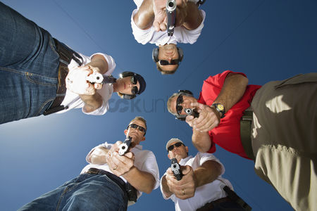 Firing : Group of people aiming guns in circle low angle view