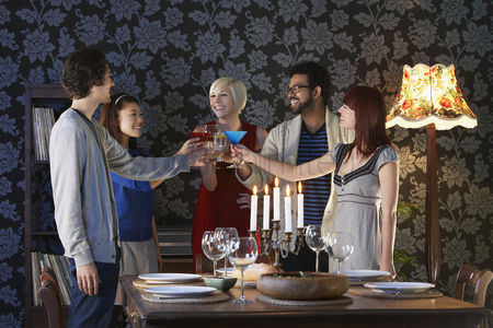 Toasting : Group of people toasting standing by dining table