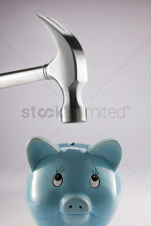 Conceptual : Hammer on top of a piggy bank